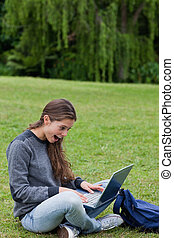 Young girl showing her surprise while looking at her laptop and sitting on the grass