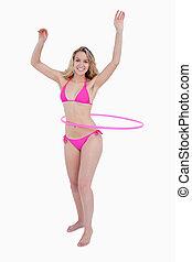 Beautiful teenager in beachwear playing hula-hoop