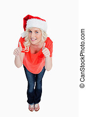 Blonde woman putting her thumbs up in satisfaction while wearing Christmas clothes