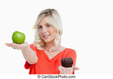 Woman looking at her favorite food between apple and muffin...