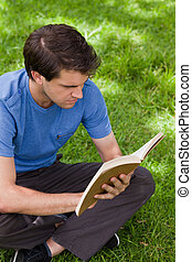 Young serious man sitting cross-legged while reading a book