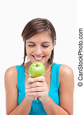 Smiling teenager crossing her hands with a green apple placed on it
