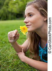 Young girl lying on the grass while smelling a flower -...