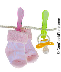 baby pink socks with pacifier hanging on rope isolated