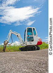 Small caterpillar tractor stands on the asphalt against the...