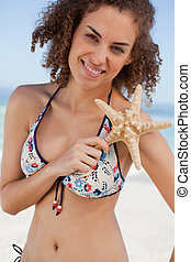 Young woman holding a beautiful starfish in front of her shoulder on the beach