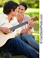 Woman smiling while her friend plays the guitar