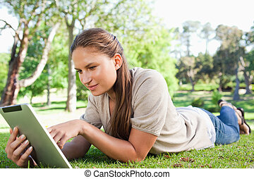 Woman with a tablet computer lying on the lawn - Young woman...