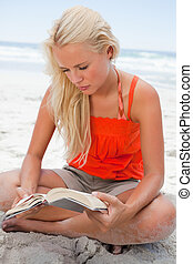 Young blonde woman sitting cross-legged while reading a book...