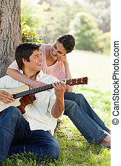 Woman looking at her friend and resting her arm on his chest while he plays a guitar under a tree