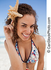 Young woman leaning her head forward while holding a starfish