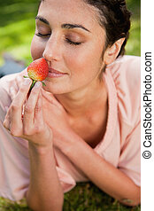 Woman smells an strawberry while lying in grass - Young...