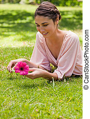 Woman lying on her front while holding a flower - Smiling...
