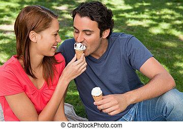 Woman feeding her friend ice cream - Smiling woman feeding...