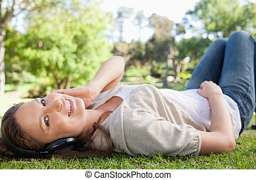 Smiling woman lying on the lawn while listening to music