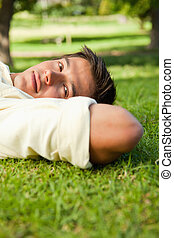 Man with serious expression lying in grass with his hands resting underneath the side of his head