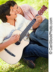 Man playing the guitar while his friend leans on his shoulder