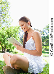 Side view of a smiling young woman using a tablet computer in the park