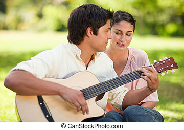 Woman listens to her friend play the guitar as they both sit next to each other on the grass