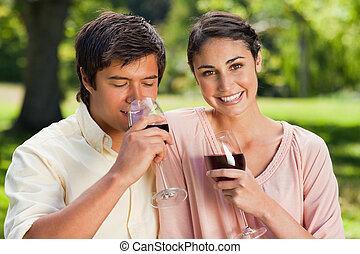 Woman smiling while her friend is drinking wine