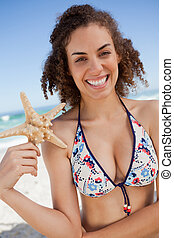 Smiling young woman discovering a starfish on the beach