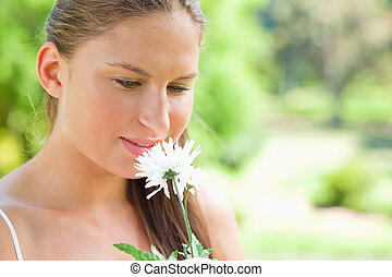 Woman smelling on a white flower in the park