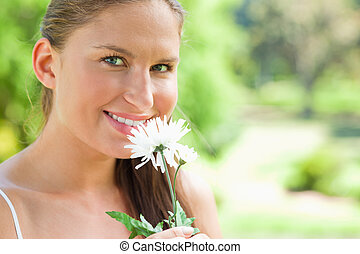 Smiling woman with a flower in the park