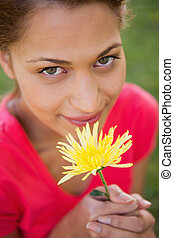 Woman looking upwards while holding a yellow flower - Woman...