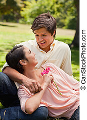 Smiling woman holding a pink flower while lying against her friend who is looking into her eyes as he sits down on the grass