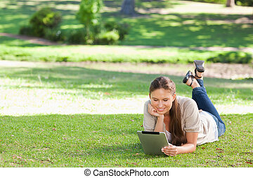 Woman laying on the lawn with a tablet computer - Young...