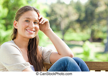 Smiling woman on a bench in the park