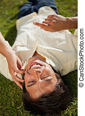 Man with his hand raised laughing while making a call over the phone as he lies down on the grass