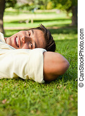 Man smiling while lying in grass with his hands resting underneath the side of his head