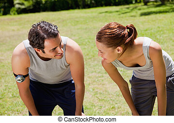 Man and a woman bending over while looking at each other -...