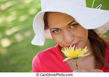 Woman wearing a white hat while smelling a yellow flower -...