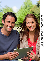 Man and a woman look ahead while holding a tablet in a sunny...