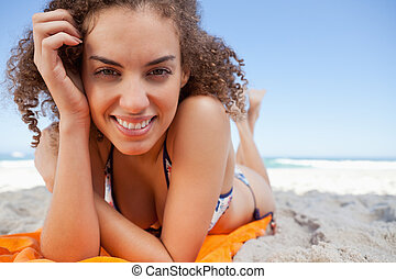 Young woman lying on beach towel while smiling with her hand on her temple