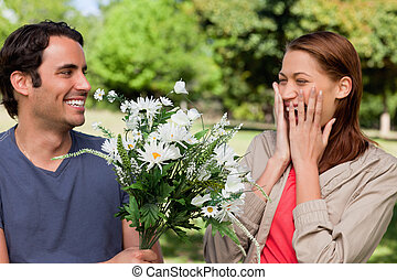 Young woman holding her hands against her face ecstatically as presented with flowers by her friend in a sunny park environment
