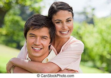 Woman smiling with her friend who is carrying her
