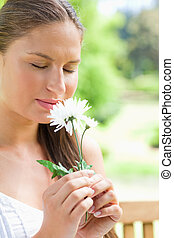 Close up of a woman smelling a flower in the park