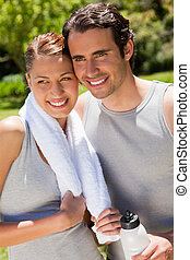 Man holding a sports bottle smiling with a woman