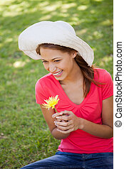 Woman wearing a white hat while holding a yellow flower -...