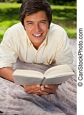 Man smiling while reading a book as he lies on a blanket -...
