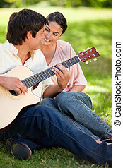 Woman smiling while watching her friend play the guitar