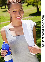 Woman smiling while holding a sports bottle