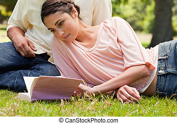 Woman lying down next to her friend while reading a book