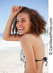 Smiling woman placing her hand on her forehead and standing in front of the sea