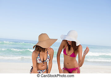 Young attractive women standing upright together in front of the