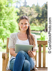 Smiling woman on a park bench with a tablet computer -...