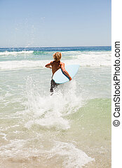 Young blonde man wading in the water while holding his blue surfboard